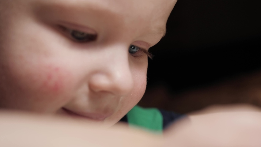 Baby plays with phone. Close-up of face of child who is intently playing with smartphone and tapping screen with his fingers. Slow motion   Shutterstock HD Video #1068620870