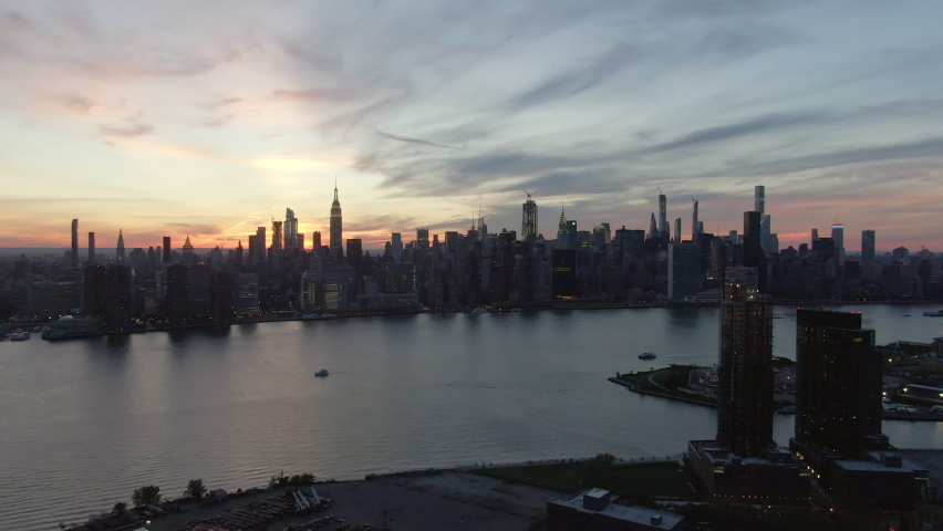 Aerial zoom in shot of modern buildings in Manhattan by East river, drone flying over city against sky during sunset - New York City, New York | Shutterstock HD Video #1068648155