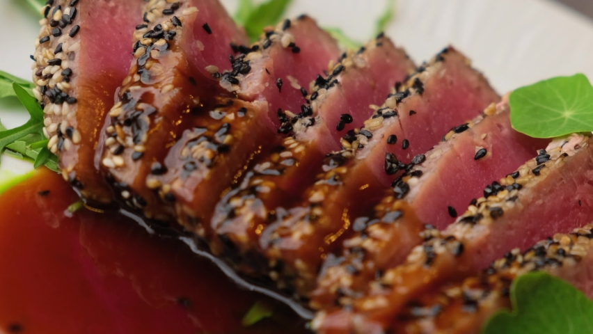 A close-up look of freshly made Sesame Crusted Tuna, Seared Tuna in 4K. Concept of cooked tuna with vegetables and sesame seeds nicely decorated by the chef in a serving plate on the table. | Shutterstock HD Video #1068657845