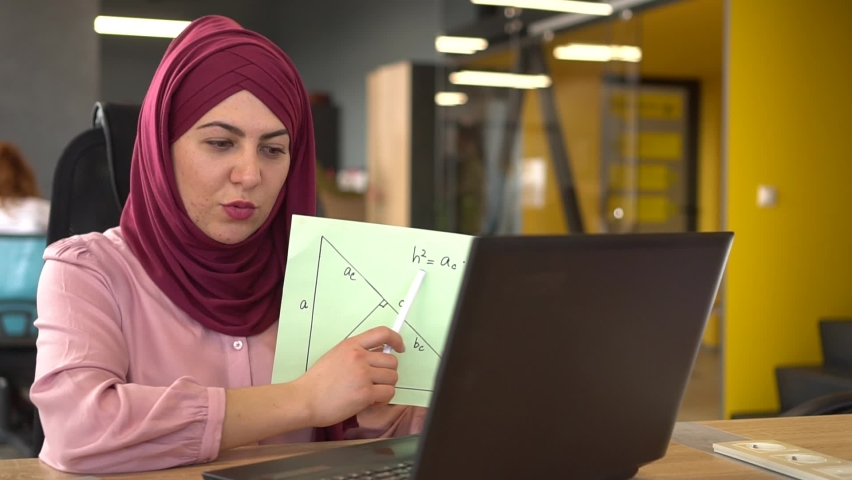 Muslim woman teacher working remotely. Online chat with students  using laptop and webcam, math lesson. Distance learning, Remote work, freelance. Covid-19 lockdown Royalty-Free Stock Footage #1068669359