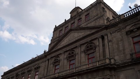 Low-angle view of baroque building from downtown Mexico City under slightly cloudy sky. Smooth view of majestic Hispanic building with classic architecture. Mexican landmarks