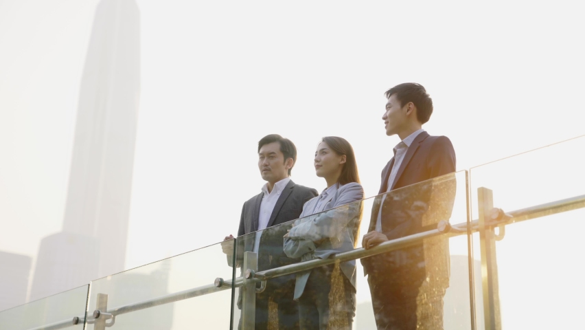 three of three asian corporate executives discussing business outdoors Royalty-Free Stock Footage #1068682697