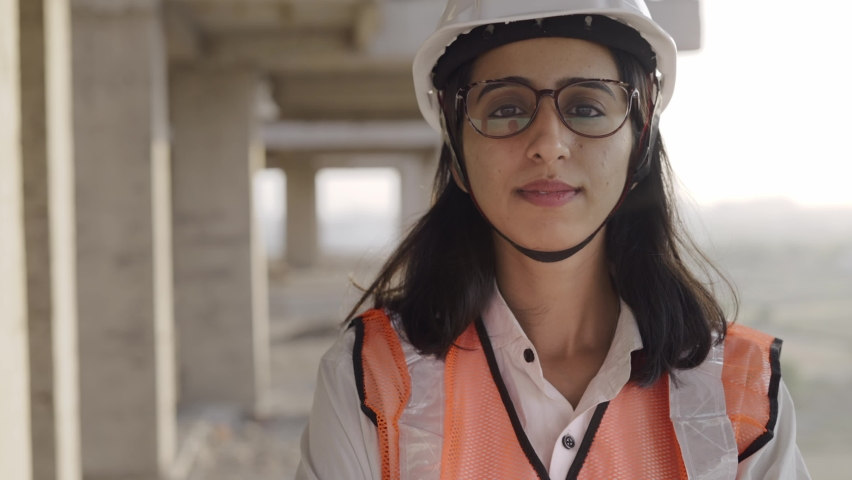 Track in a close-up shot of a young confident Indian Asian female civil engineer wearing a safety helmet standing with folded arms and looking at the camera on top of an under-construction building. Royalty-Free Stock Footage #1068692603