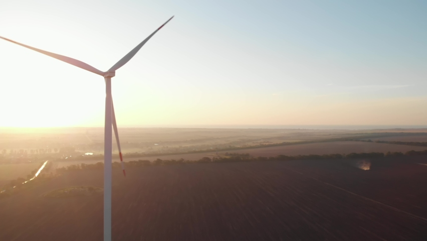 Wind turbines power plant aerial sunset view green energy. Wind mills rotating generating renewable energy at golden hour light flares. Cinematic rural green energy 4K | Shutterstock HD Video #1068695807