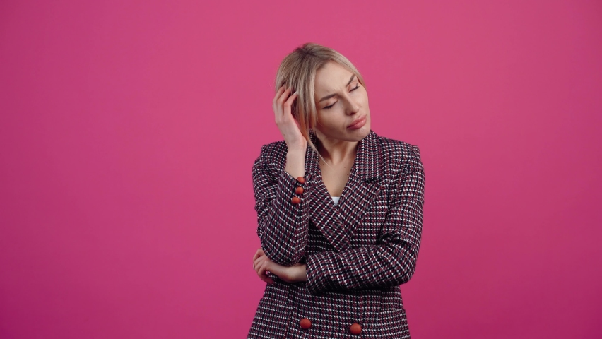 The mature woman who meditates on new possibilities, new ideas, new concepts of achievement, finally smiles fulfilled. Beautiful young mature blonde in pink jacket. Isolated on a pink background | Shutterstock HD Video #1068712031