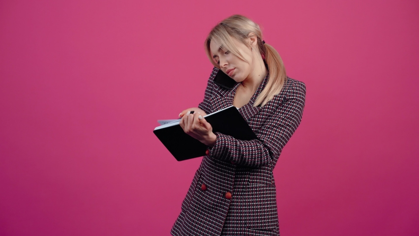 Businesswoman, young woman talks on the phone and records information in the notebook, at the end she smiles widely. Beautiful young mature blonde in pink jacket. Isolated on a pink background | Shutterstock HD Video #1068712037