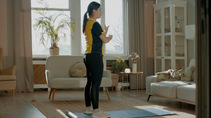A little overweight Asian Korean female working out at home, doing some fitness exercises. Shot with 2x anamorphic lens | Shutterstock HD Video #1068715844