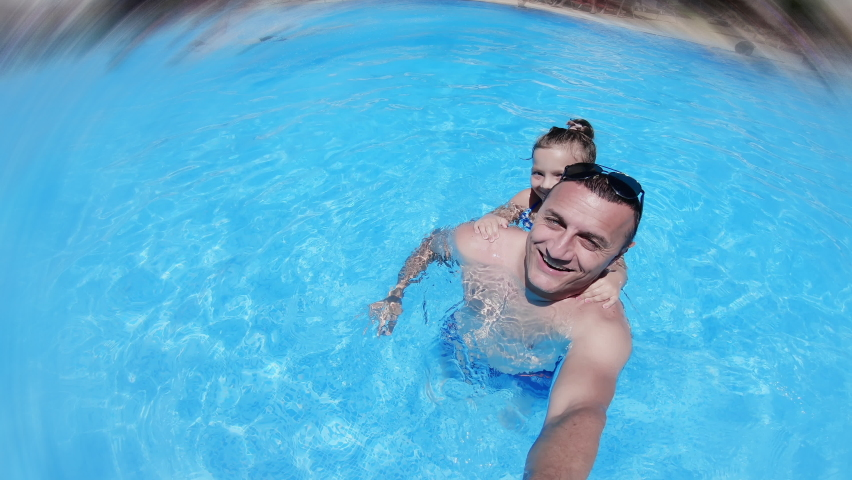 Happy family father with daughter smiling, spinning while swimming in pool outdoor during summer vacation