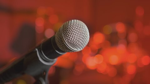 Microphone on stage in nightclub or karaoke bar on blurred red background in lights of color music close up.