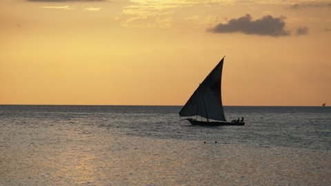 Silhouette of a traditional sailing boat Dhow sailing at sunset on the shore beach, Zanzibar. Amazing landscape of fishermen's wooden Boat with sail set on a background of orange sky. Africa. 4K.