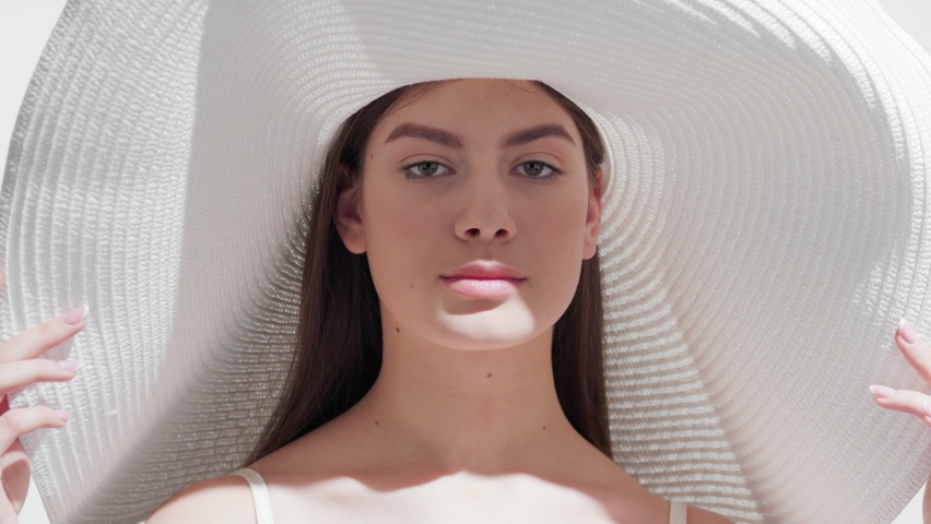 Young pretty brown-haired European woman in a big white hat holding the brim of it blows a kiss for the camera and smiles wide touching her face against white background | Face skin protection concept