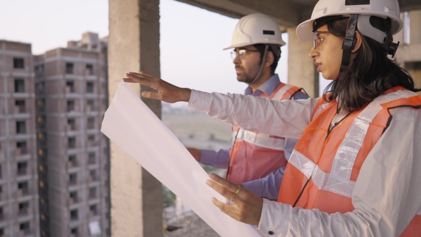 A young male and female Indian Asian civil engineers safety jackets and helmets standing on an under-construction building holding a blueprint of the structure and working together   Royalty-Free Stock Footage #1068774254