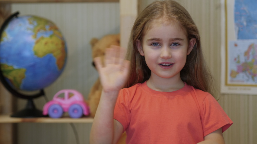 Kid Child Girl Making Online Video Call Recording Vlog Sitting by  Table , Portrait. Funny Girl Smiling Looking At Camera. Happy Cute Little Vlogger Saying Hello Hi Looking At Camera Talking To Webcam Royalty-Free Stock Footage #1068781070