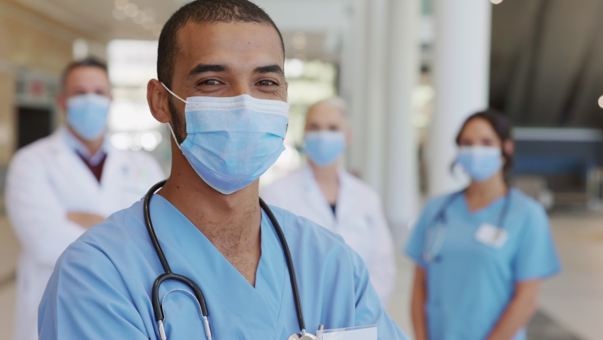 Confident male nurse in front of his medical team looking at camera wearing face mask during Covid19 pandemic. Smiling middle eastern surgeon standing in front of colleagues wearing protective mask. Royalty-Free Stock Footage #1068792179