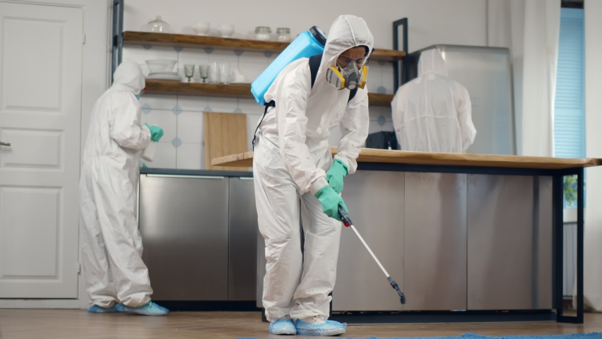 Home disinfection by commercial disinfecting services. Team of specialists in safety overall and mask disinfecting apartment with detergent spray during covid-19 epidemic Royalty-Free Stock Footage #1068801578