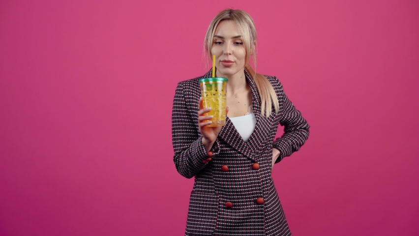 The cheerful young woman, with a fresh glass in her hand, smiles, drinks a little of it and finally recommends it. Beautiful young mature blonde in pink jacket. Isolated on a pink background. Concept | Shutterstock HD Video #1068809198