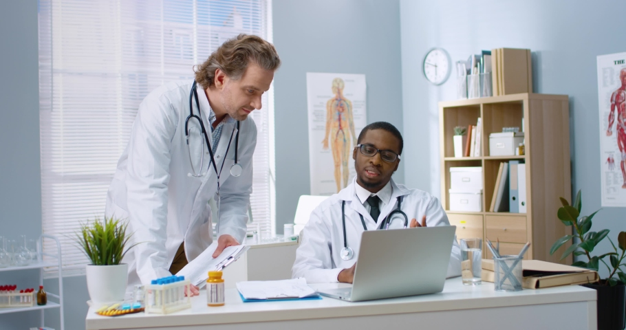 Caucasian man doctor stands near African American young physician in cabinet in clinic speaking and consulting tapping on computer looking at screen and discussing disease treatment healthcare workers Royalty-Free Stock Footage #1068813488