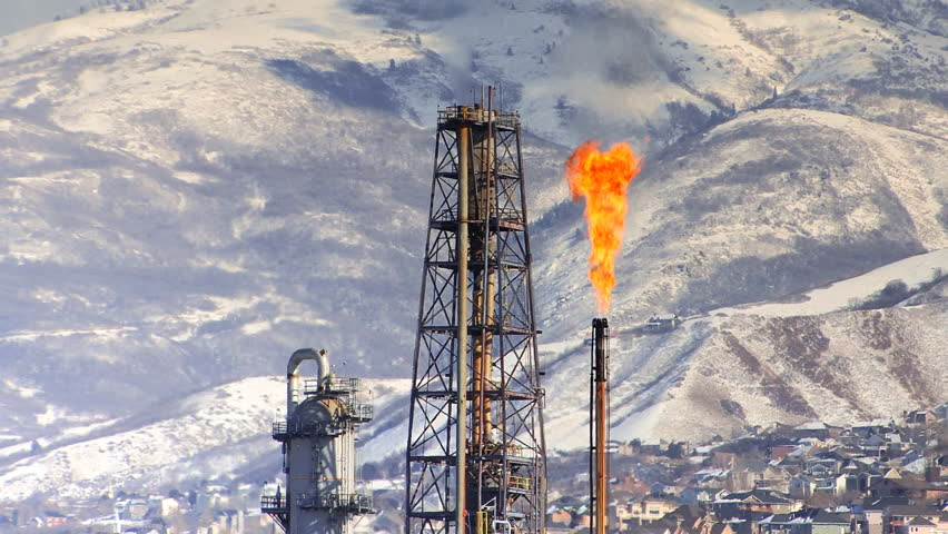 Refinery flame with snow covered mountains behind | Shutterstock HD Video #1068826
