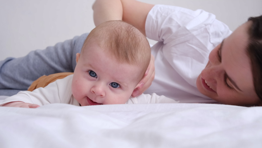 Happy caucasian mother kisses and gently strokes cute baby daughter lying together on cozy bed at home. Joyful young mom hugging little toddler girl feeling love and tenderness. Motherhood concept