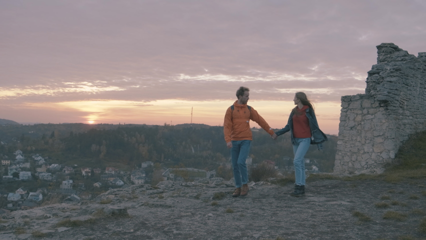 Wanderlust. Young female and male find ruins of an ancient castle. Beautiful sunset. | Shutterstock HD Video #1068839333