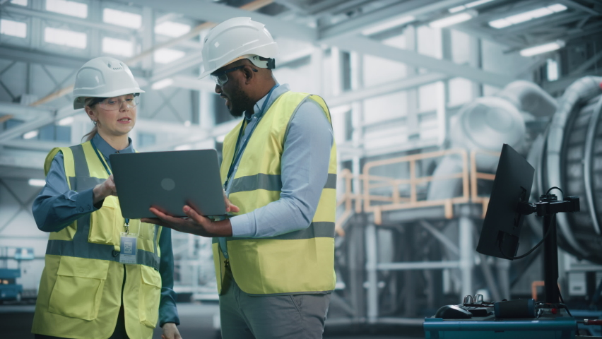 Two Diverse Professional Heavy Industry Engineers Wearing Safety Uniform and Hard Hats Working on Laptop Computer. African American Technician and Female Worker Talking on a Meeting in a Factory. Royalty-Free Stock Footage #1068840050