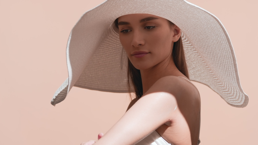 Young pretty European woman with long brown hair in a big white hat and white bikini applies sun cream on her body and enjoys the sun touching her hat against beige background | Sunscreen commercial