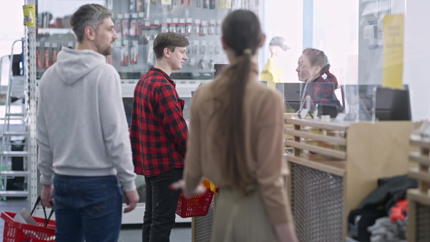 Queue arguing with buyer standing at cashier in hardware store. Irritated Caucasian men and woman shouting and gesturing buying tools and supplies in shop indoors. Conflict and consumerism.