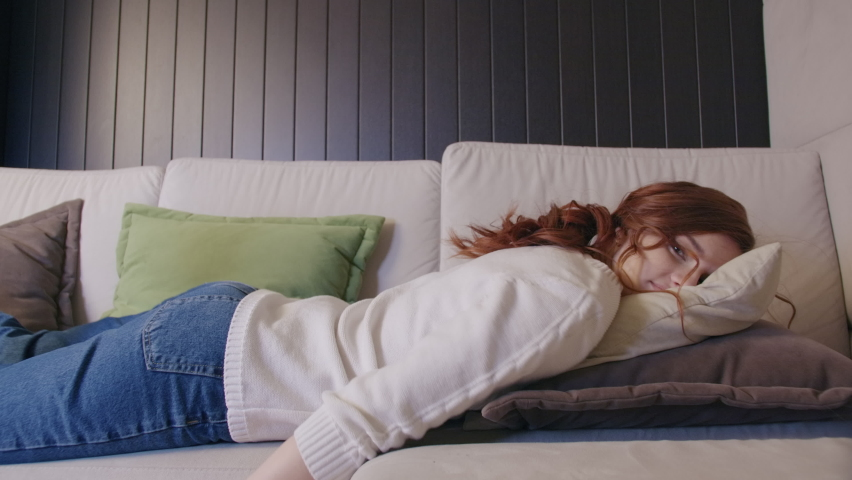 Exhausted Or Bored Young Sleepy Woman Falls Down On Sofa. Apathetic Tired Lazy Lady Sleeping On Couch At Home Alone. Funny Girl Lying Asleep Feeling Lack Of Motivation, Fatigue Or Depression Concept Royalty-Free Stock Footage #1068895034