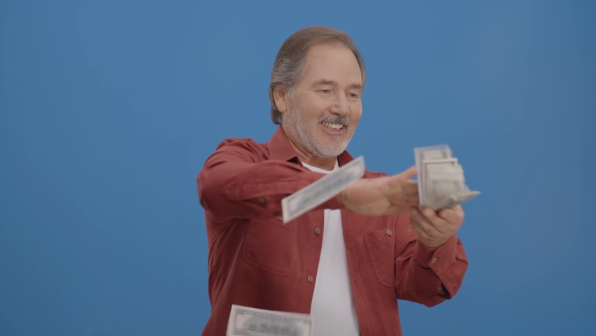Old man with beard in front of a blue background who is cheerfully gesturing while handing out money. Concept of to pour money without thinking. It makes it rain by throwing money into the air.  Royalty-Free Stock Footage #1068942296
