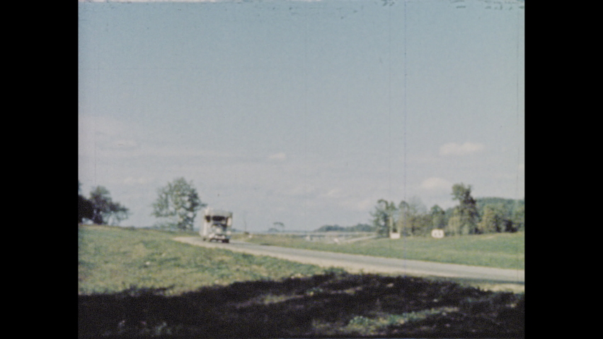 1950s: Man narrates story of arrival in trailer village community as chrome mobile home arrives passes down highway and pulls into village.