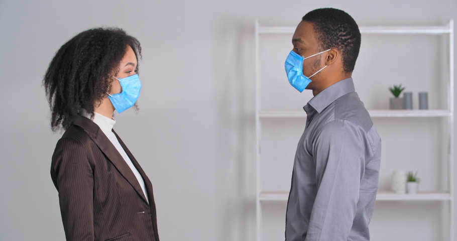 African american businesswoman and black businessman wear medical face masks greeting with elbow bump work together in office show ok sign thumb up gesture. Two colleagues doing coronavirus greeting Royalty-Free Stock Footage #1068966607