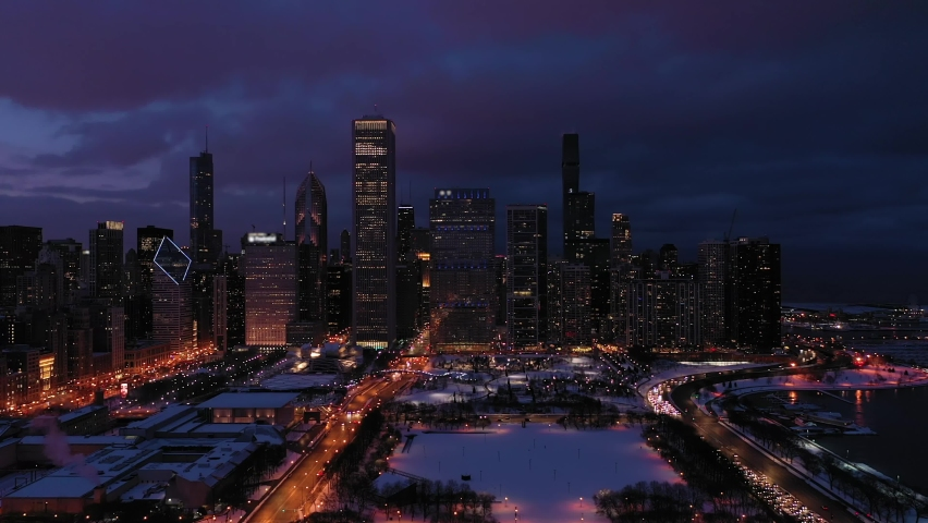 Urban Skyline of Chicago Loop at Night in Winter. New Eastside and Lake Michigan. Blue Hour. Aerial View. United States of America. Drone Flies Sideways and Upwards