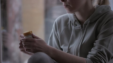Close-up of a woman opens a jar of dietary supplements and takes out a capsule