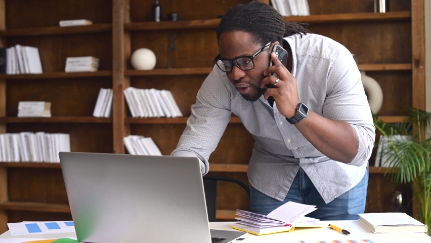 Busy young African-American male office worker wearing glasses standing near the desk, has a phone call and typing on laptop, multitasking guy working on a project in a modern office | Shutterstock HD Video #1068983557