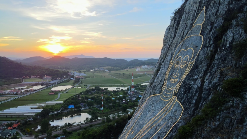 4k Aerial Medium shot Pan left at Buddha Mountain in Pattaya at Sunrise. Drone shot: image of Buddha engraved with gold into the hill in Khao Chi Chan, Chonburi, Thailand. Cinematic thai attractions. Royalty-Free Stock Footage #1069006963