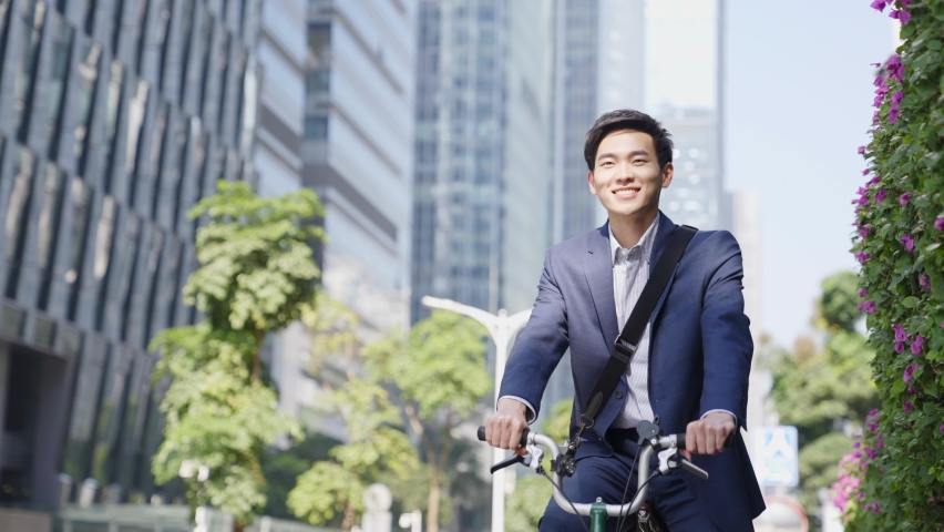 Young asian business man riding bike to work in downtown of modern city | Shutterstock HD Video #1069015072