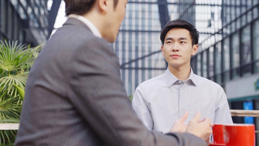 two asian business men sitting talking discussing in outdoor coffee shop Royalty-Free Stock Footage #1069015081
