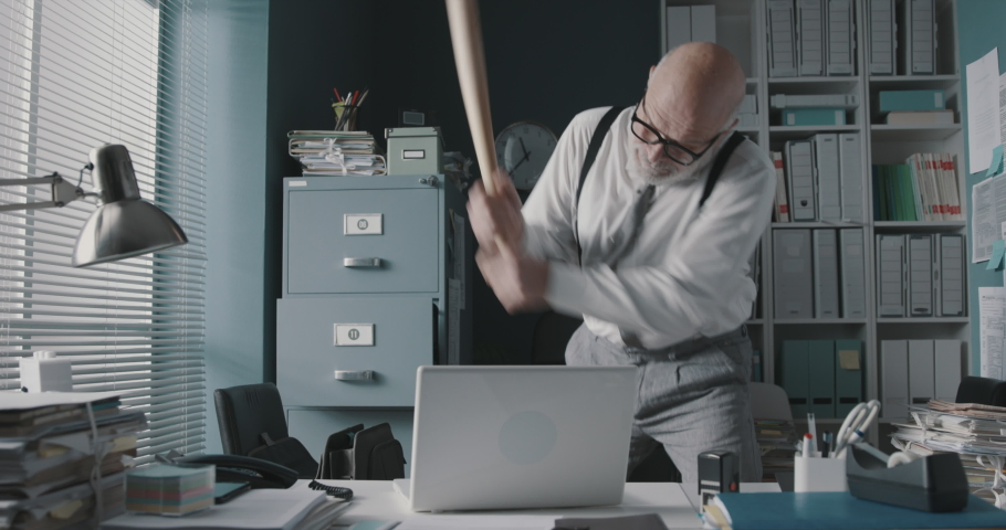 Stressed angry businessman smashing his laptop with a baseball bat, job burnout concept