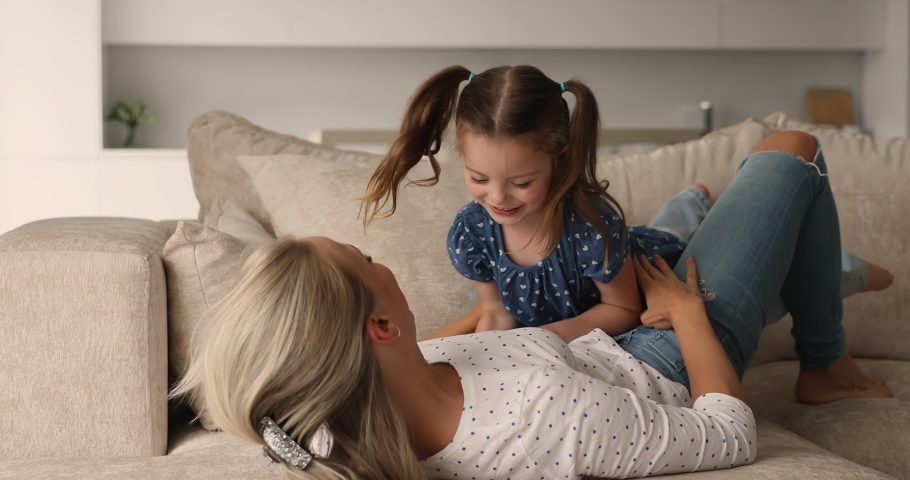 Cheerful mom play with little daughter at home, happy active family lying on comfy cozy sofa in modern living room, spend free weekend time together enjoy playtime and communication. Bond, fun concept Royalty-Free Stock Footage #1069058647