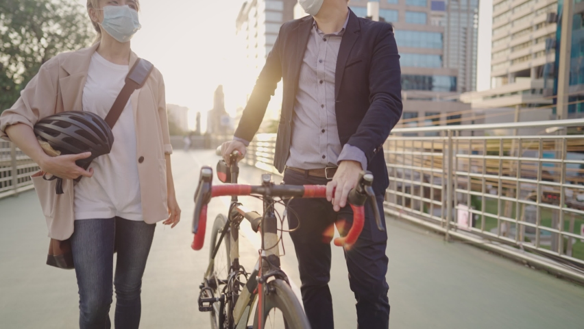 Young active cheerful workers chatting and smiling walking home on bicycle way on city overpass, after successful working, healthy couple decided to save monthly expenses cost includes daily exercise Royalty-Free Stock Footage #1069087753