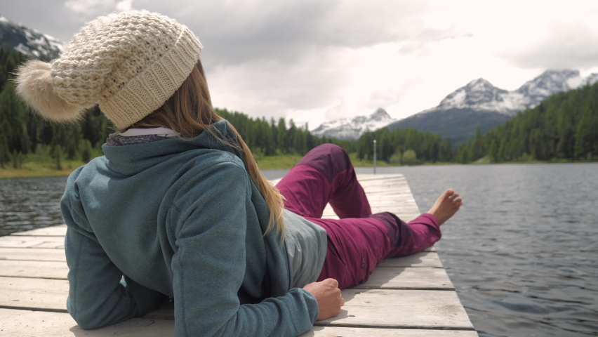 Woman on a hike in the mountains relaxes on wooden jetty above Alpine lake  | Shutterstock HD Video #1069091137