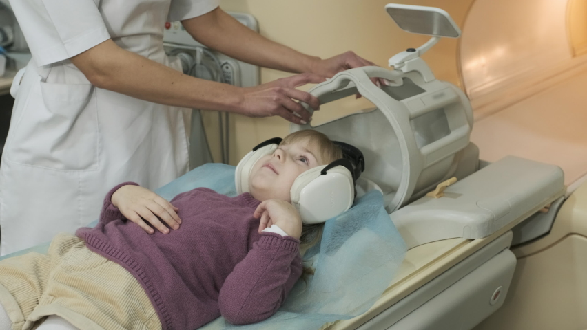 Doctor radiologist puts coil on the head of the patient little girl to make an MRI scanning of brain, head, neck, girl lies on automatic table, using modern equipment | Shutterstock HD Video #1069097563