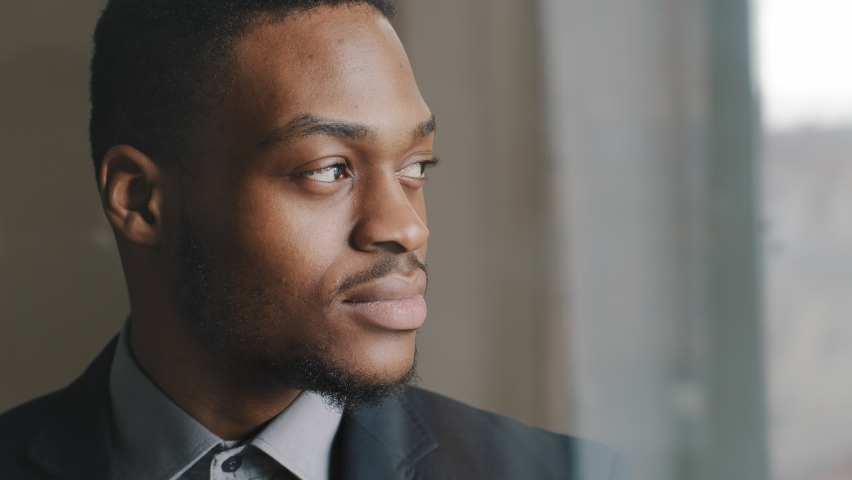 Close-up black serious male face in profile, concentrated expression, portrait of pensive afro american business man boss looking out window in office thinking making decision turns his head to thecamera. Royalty-Free Stock Footage #1069097809