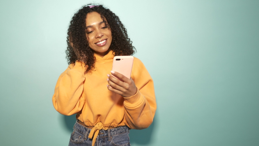 Beautiful black woman with afro curls hairstyle.Smiling model in orange hoodie and jeans.Sexy carefree female listening music in wireless headphones.Posing in studio near blue wall