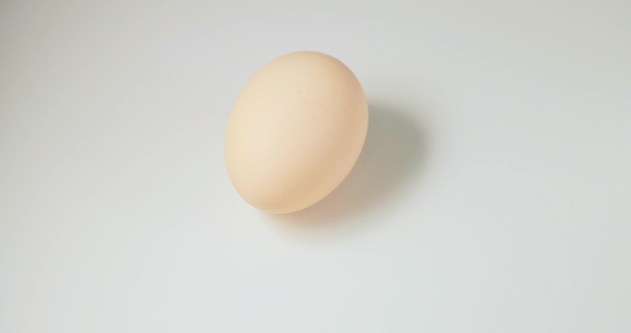 Chicken egg rotates on a white background. slow motion. | Shutterstock HD Video #1069118938