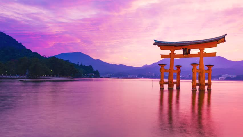 Sunset time-lapse of the famous orange shinto gate (Torii) of Miyajima island of Hiroshima prefecture, Japan.