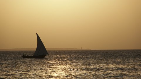 Silhouette of African excursion wooden Dhow boat sailing with tourists in the waters of the Indian Ocean. Zanzibar, Tanzania. Rustic traditional boat rocking on waves. Boat trip in Africa. Sea horizon