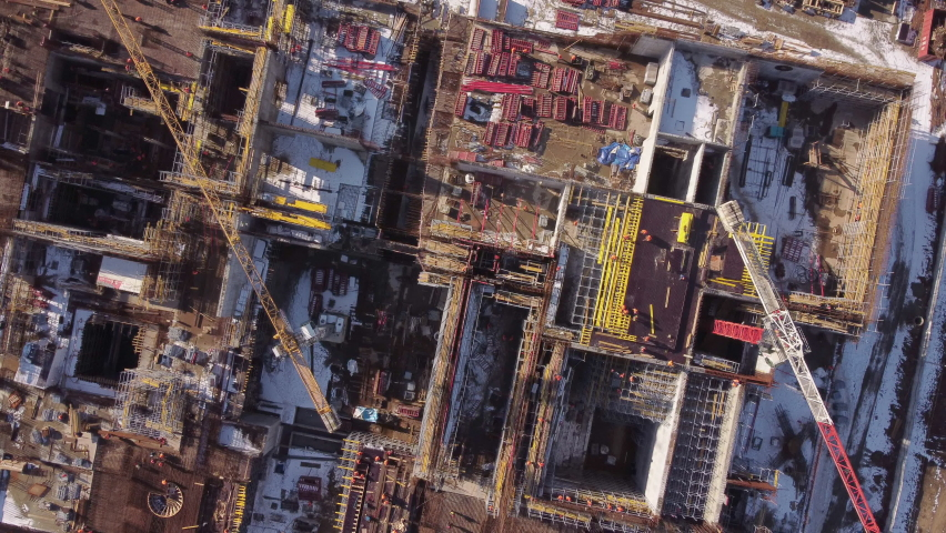 Aerial drone view with rotation over industrial factory under construction with cranes and workpeople | Shutterstock HD Video #1069163257