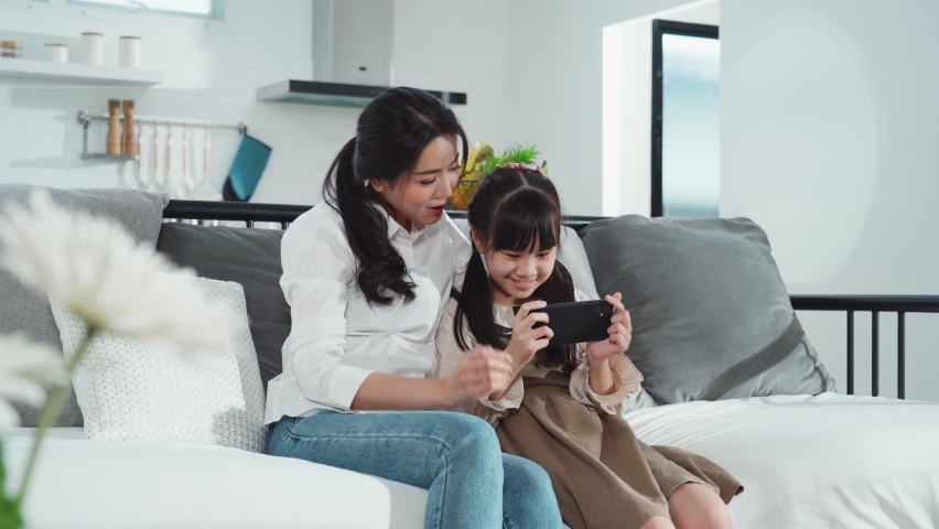 Asian family mother and daughter sitting on sofa enjoy playing game on smartphone together in living room at home with happiness and smile. Happy activity technology lifestyle mobile phone use concept | Shutterstock HD Video #1069167448