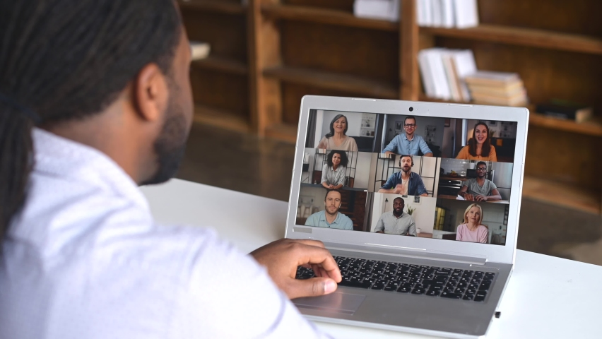Close-up of African American man with dreadlocks using app for distance video communication with coworkers, friends, meeting online, looking and waving at laptop desktop with people profiles | Shutterstock HD Video #1069171588